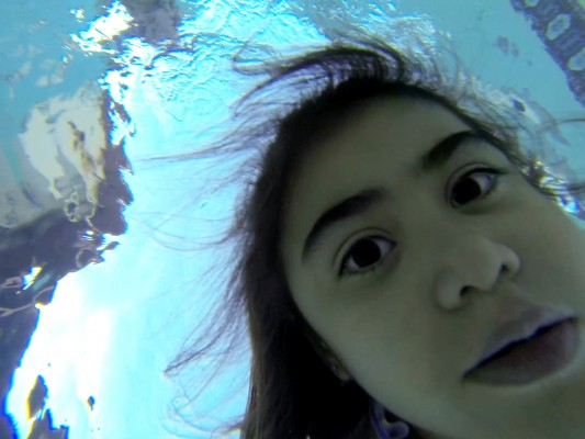 Chanielle Islas underwater in my backyard swimming pool looking down at a GoPro Hero3 camera in her hand.