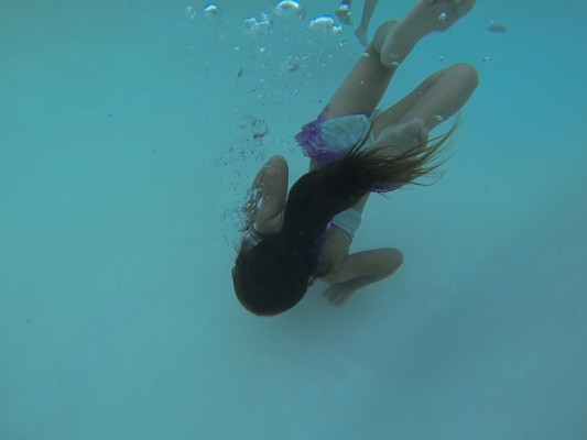 GoPro Hero3 photo looking down in pool as 5-year-old girl swims across the bottom of the pool with her hair flowing behind her.
