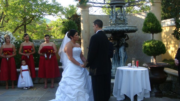 Christie Farrell Perez and Kevin Perez hold hands during their wedding ceremony.