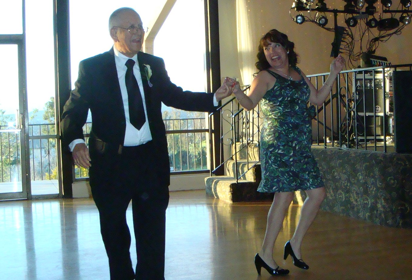 A man in a black suit dancing with a woman in a dark-print, knee-length dress and black heels. The are on the dance floor at a wedding reception.
