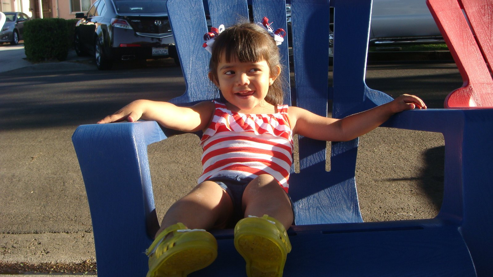 an almost 3-year-old girl in a red-and-white striped top and blue shorts sitting in a big, plastic blue chair and smiling.