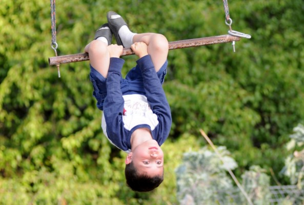 Danny Perez hanging upside down from a swing